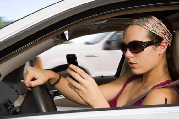 mulher dirigindo usando celular